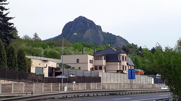 Mohutný blok hory Bořeň za domy v Bílině