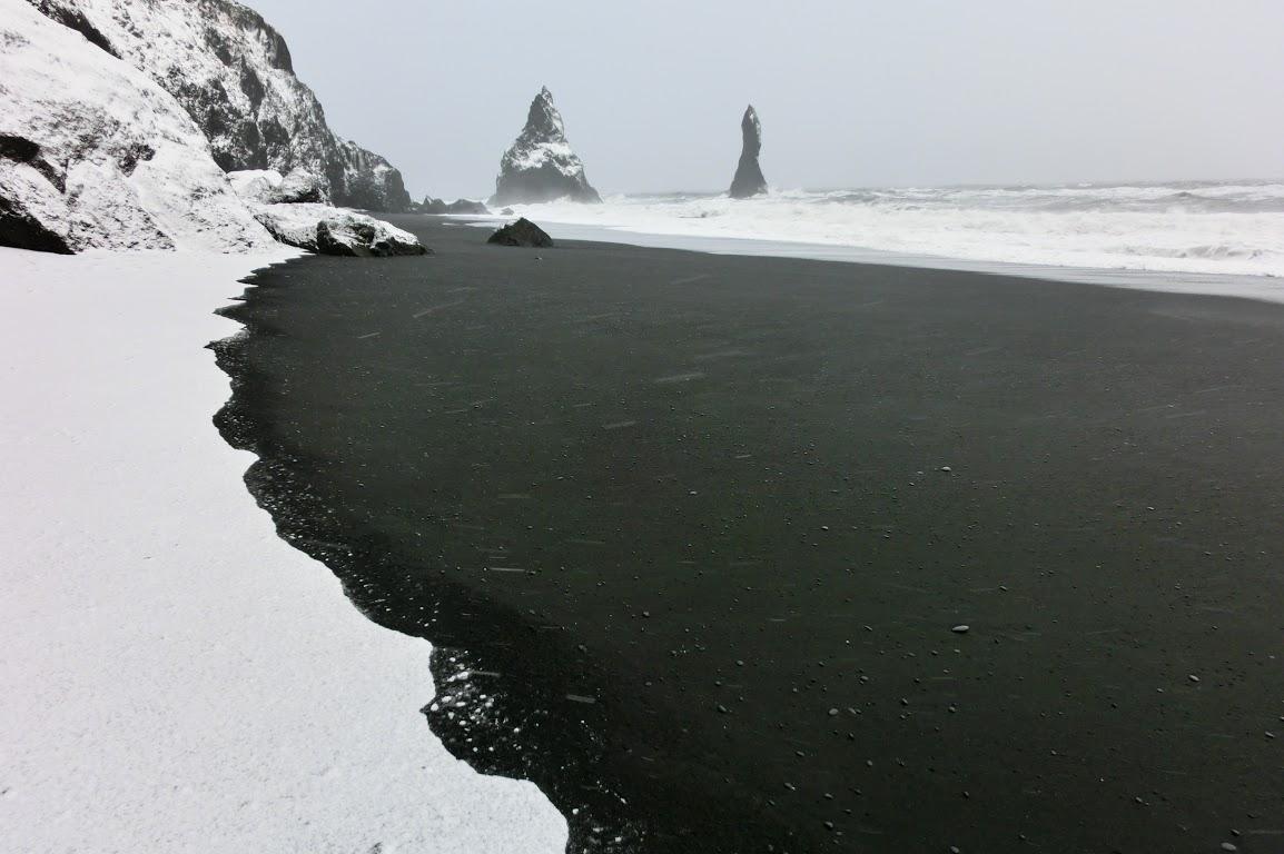 Kontrast černého písku a bílého sněhu