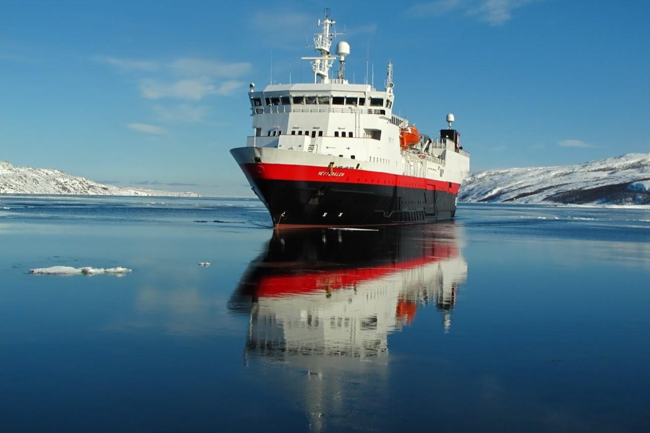 Loď společnosti Hurtigruten plující kolem pobřeží
